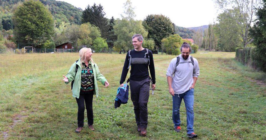 Sabine Weigand, Christian Zwanziger und Dominik Österreicher wandern über eine Wiese.