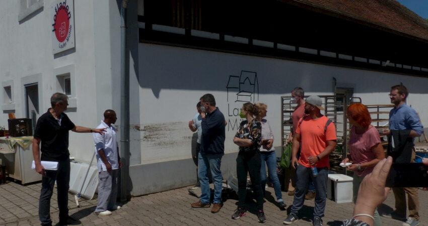 Leiter der Laufer Mühle M. Thiem zeigt den Gästen die Spuren des Hochwassers an der Außenwand der Bäckerei