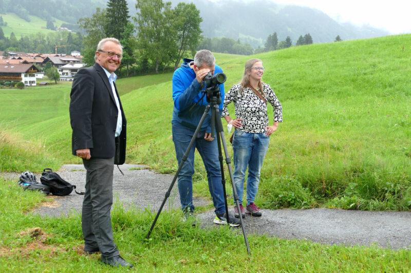 Thomas Gehring, Christian Zwanziger und Christina Mader stehen mit einem Spektiv an einem Weg.